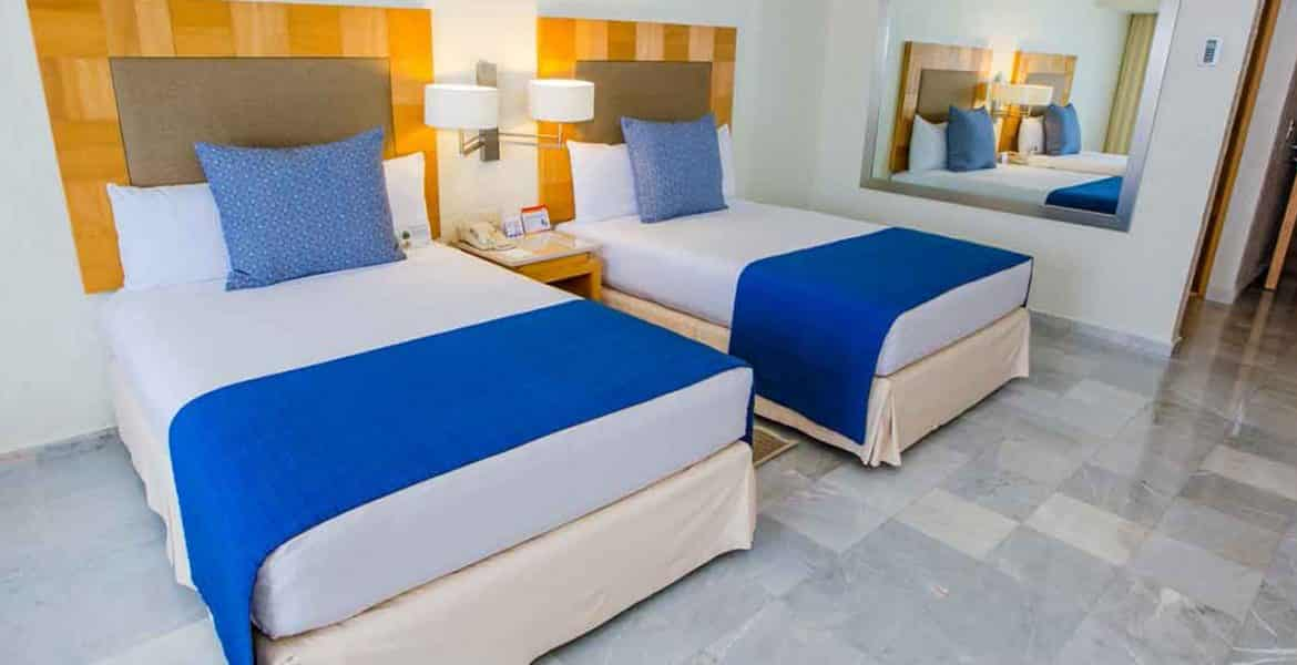 resort-suite-two-white-beds-blue-accents