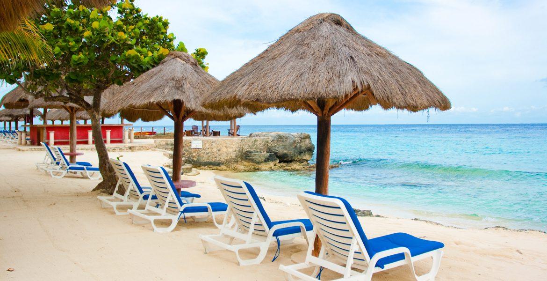 white-sand-beach-blue-loungers-tiki-umbrella-turquoise-ocean