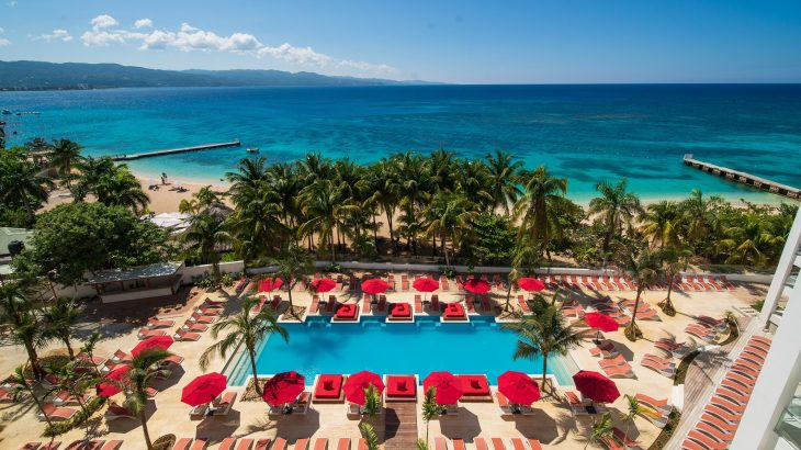 The main pool at the S Hotel Montego Bay with sunbeds and umbrelllas and the beach beyond