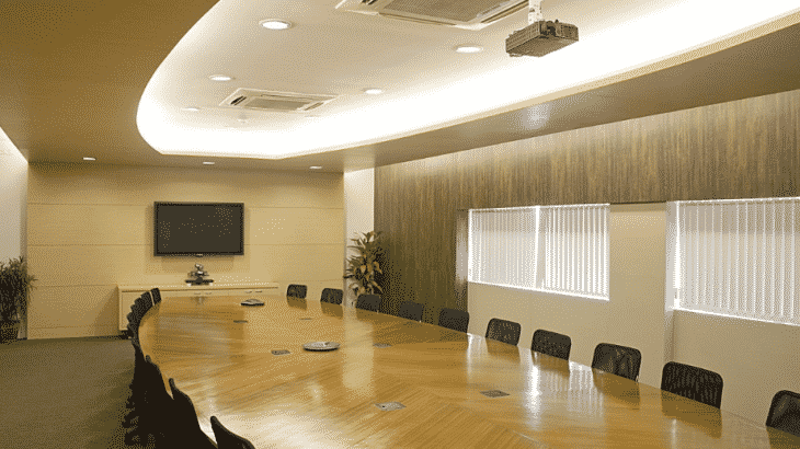 neutral-toned-conference-room-table-screen-chairs