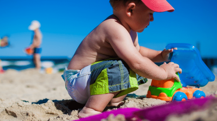boy-toddler-playing-in-sand-colorful-tools