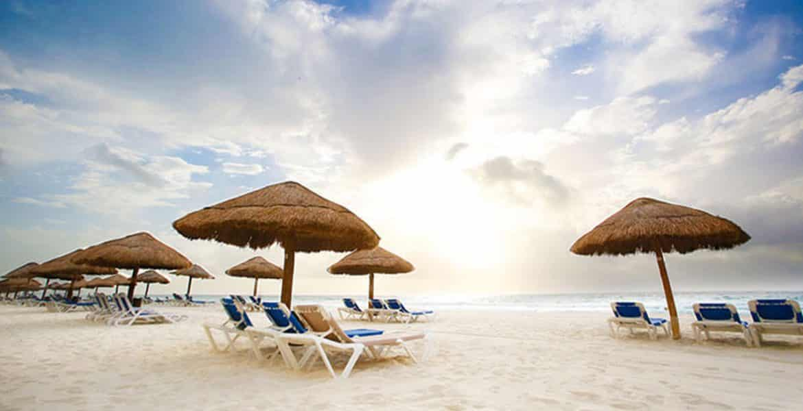 white-sand-beach-lounge-chairs-tiki-umbrellas