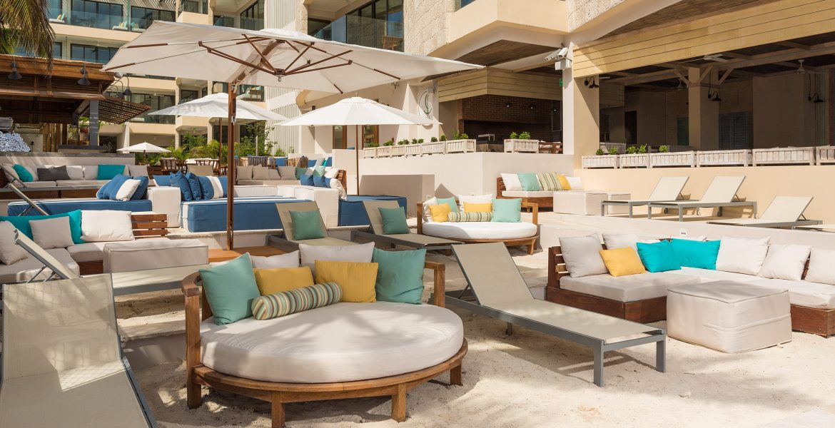 patio-seating-by-hotel-pool-couches-white-umbrella