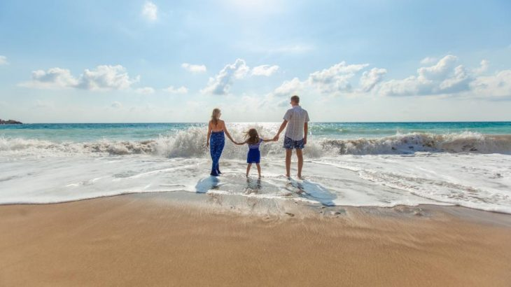 couple-holding-daughters-hands-waters-edge-beach-vacation