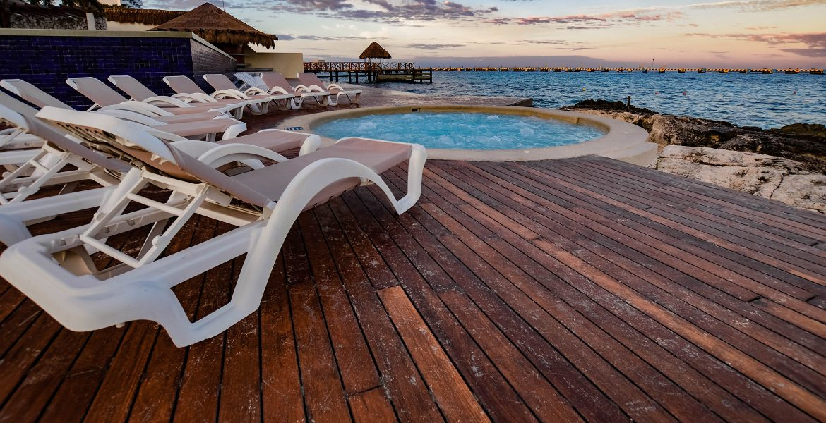 wooden-deck-white-deck-chair-blue-round-oceanfront-pool