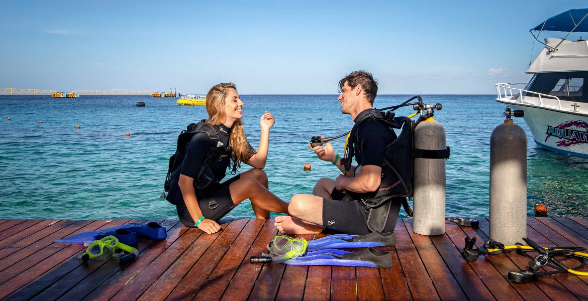 couple-going-scuba-diving-sitting-on-dock