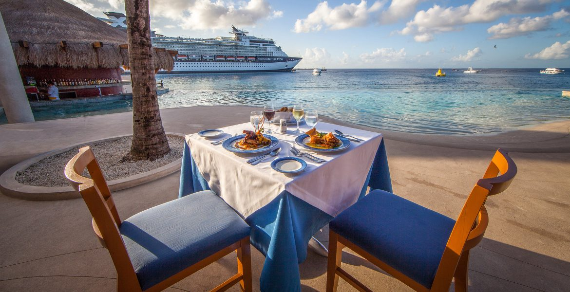 ocean-front-dining-blue-decor-food-on-table-cruise-ship-in-distance
