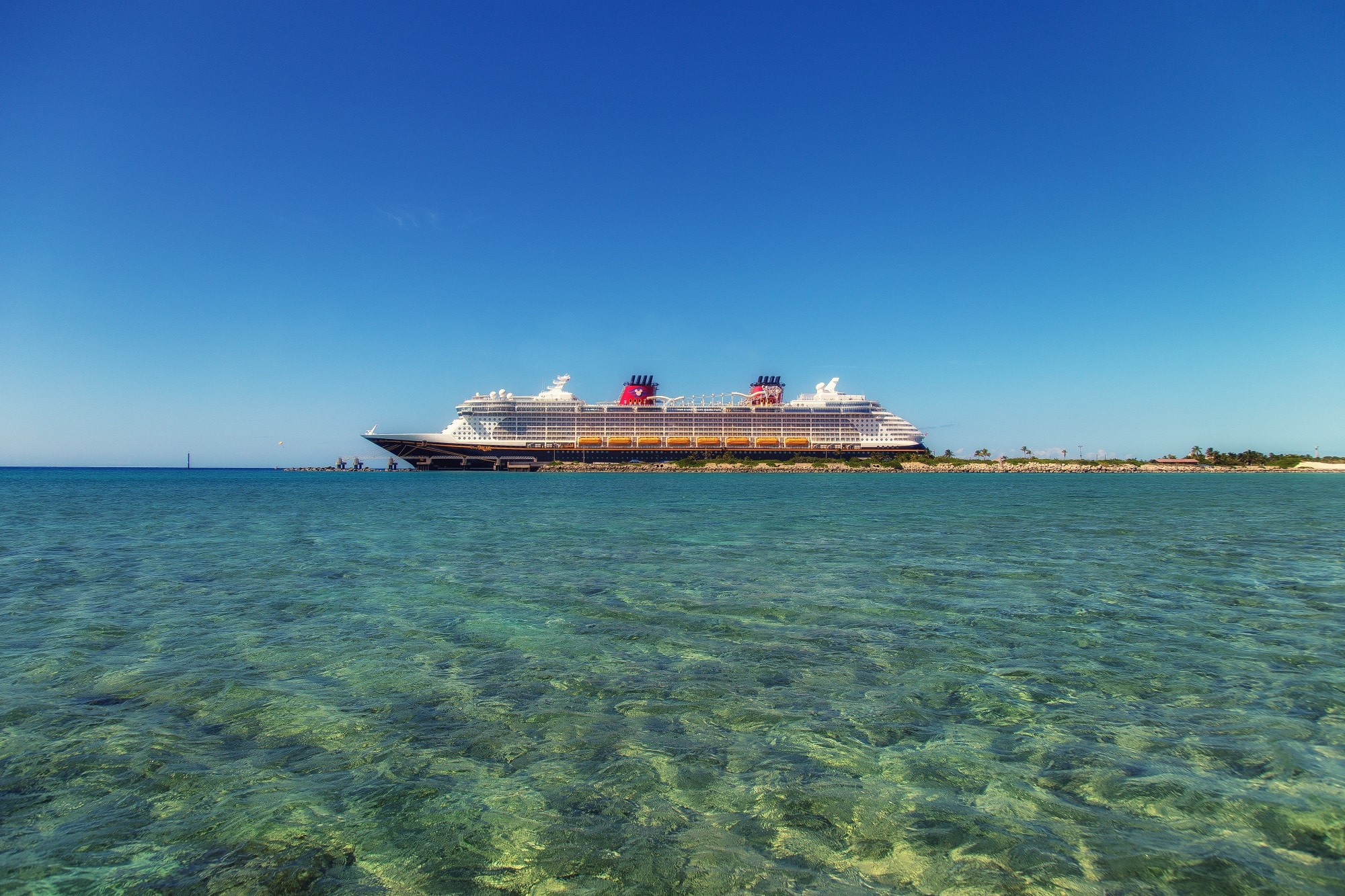 A cruise ship in shallow, crystalline blue waters