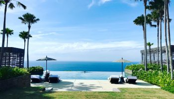 view-of-resort-infinity-pool-overlooking-ocean-palm-trees-buildings