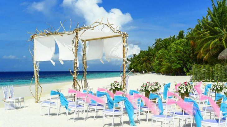 beach-wedding-set-up-chairs-archway-white-sand-blue-ocean-green-foliage