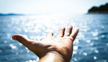 hand-reaching-out-over-ocean-sun-shining