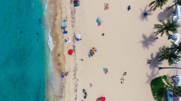 aerial-view-golden-sand-beach-colorful-umbrellas-people-turquoise-ocean