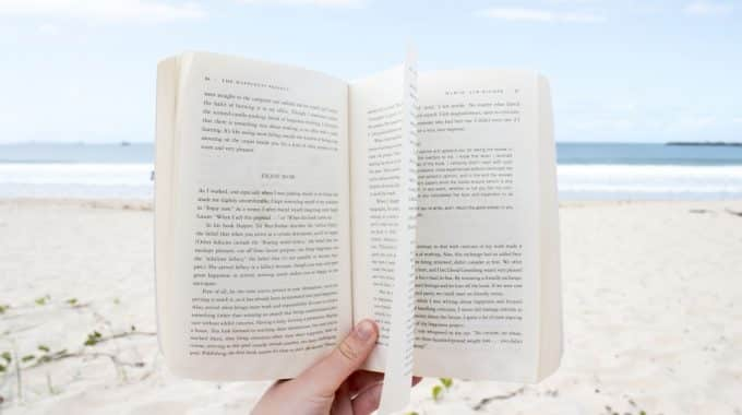 hand-holding-open-book-on-beach-sand-below