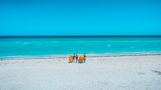 three-people-walking-on-beach-carrying-floats-to-ocean