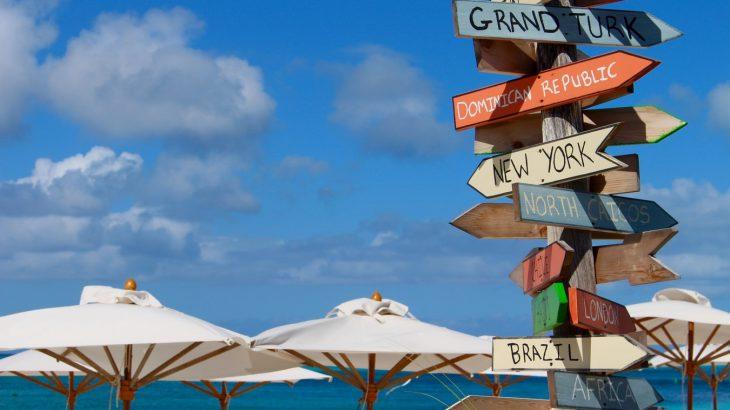 destinations-sign-on-beach-white-umbrellas-blue-sky-turks-caicos-islands