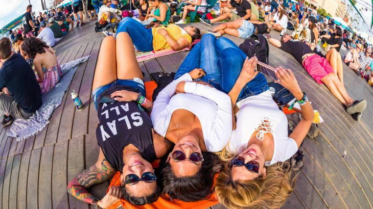 three-women-laying-on-deck-at-festival