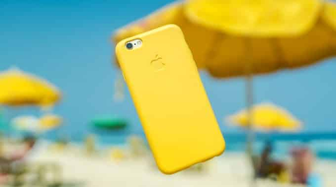 yellow-iphone-floating-beach-background-blurred-white-sand-yellow-umbrellas