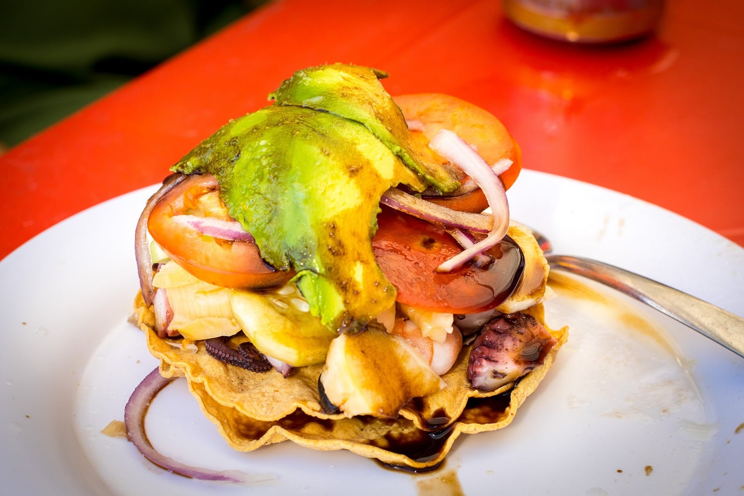 A fresh seafood dish topped with sauce, onions and avocado on a Vallarta Food Tour