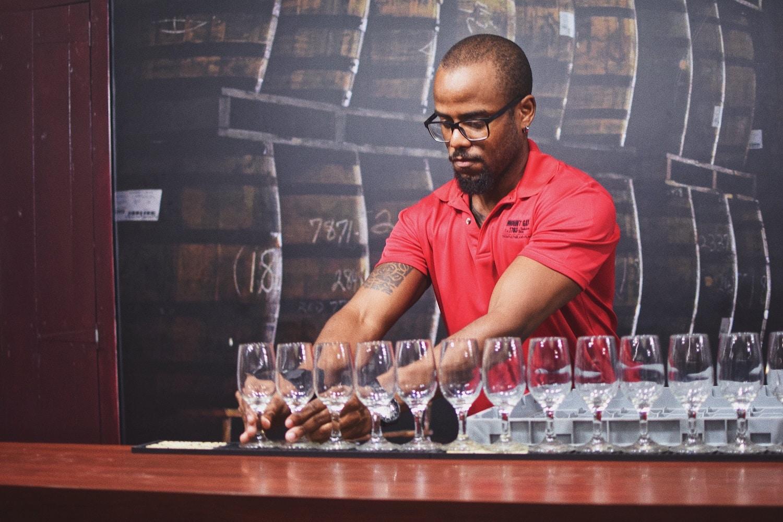 A bartender prepares tasting glasses for rum