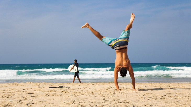 Man does cartwheel on beach in swimming trunks