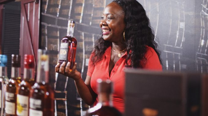 A woman holds a bottle of rum on part of the rum tour at Mount Gay - hosted with a smile