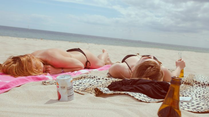 Two girls tanning on beach towels