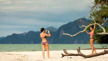 Girls taking photos on beach in bikinis