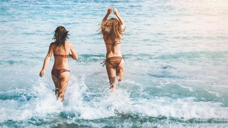 Two girls jumping in the ocean in bikini on Spring Break