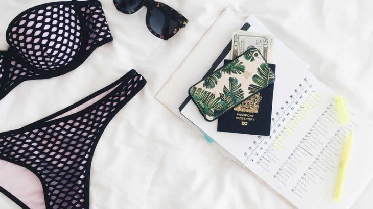 aerial-shot-bikini-passport-phone-sunglasses-on-white-spread