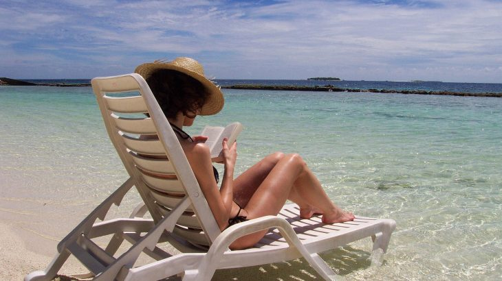 Woman sits on sun lounger in ocean reading book.