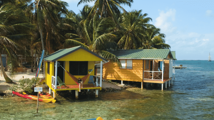 Two yellow overwater bungalows side by side with hammocks