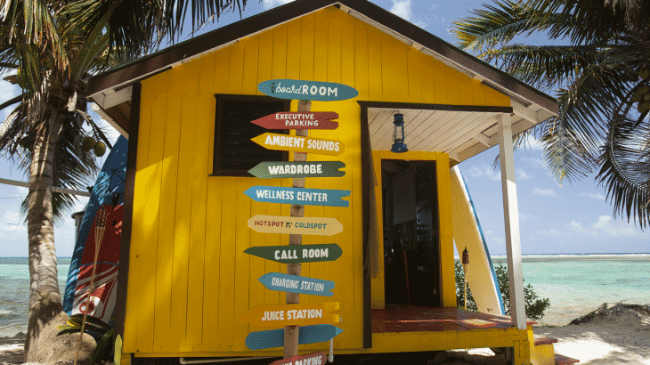 yellow bungalow on the ocean with signs pointing all directions