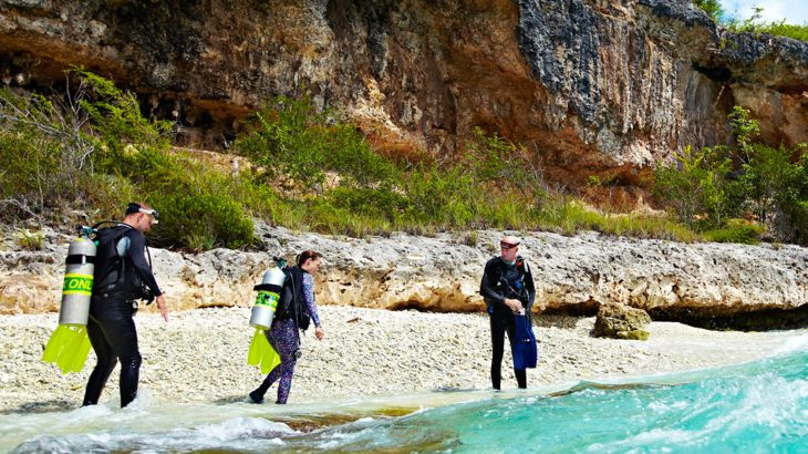 Three divers with oxygen tanks walking into blue water from a beach with huge cliffs behind them