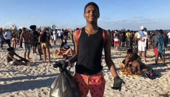 young boy picks up trash on busy Miami Beach