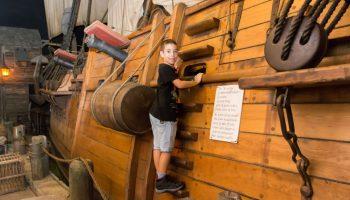 Little boy wearing black shirt playing on pirate ship at the Pirates of Nassau Museum