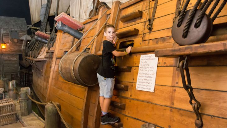 Little boy wearing black shirt playing on pirate ship at the Pirates of Nassau Museum