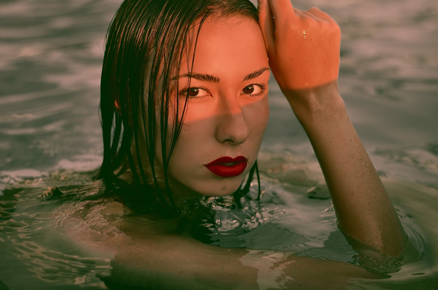 A woman swims in the ocean with red lipstick on