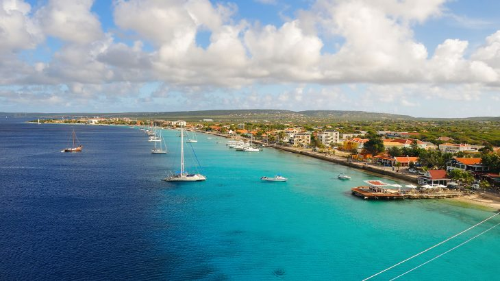 The island of Bonaire from above with blue water and sail boats and the land in the background